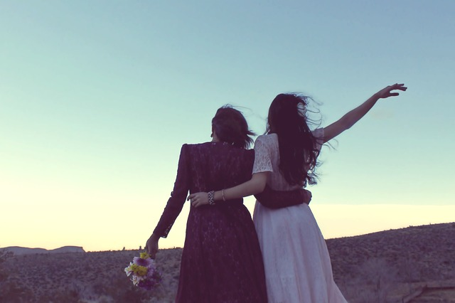 Zwei Frauen umarmen sich in Hochzeitskleidern
